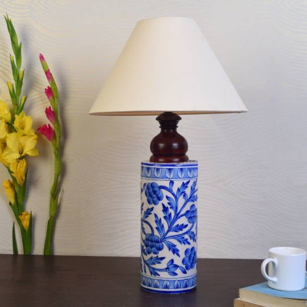 Unravel India This handpainted ceramic lamp will add an ethnic touch to your living room. Place it on the bed side table or a study table, it will equally make the place graceful. It has a cute cylindrical shape with Mugal art painting done by the artisans from Rajasthan.This work is also known as Blue pottery work.Blue pottery started during the reign of Sawai Ram Singh II during 19th century,Blue Potteryis famous for the exquisite designs and excellent craftsmanship.If you want to lift the aesthetic feel of the interior of your house, then add this lamp.It can also be giftedto family and friends and they would love it! Table Lamp
